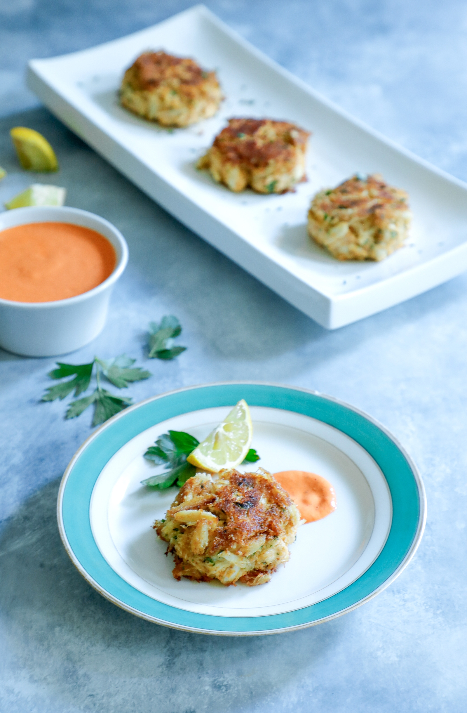 Keto crab cakes served with roasted red pepper sauce and lemon wedges.