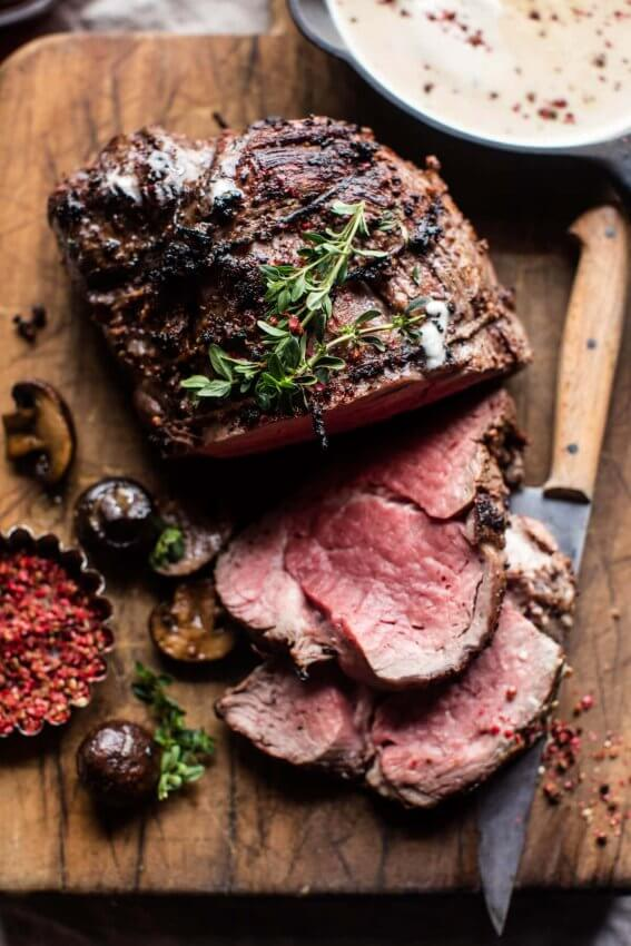 Roasted Beef Tenderloin sliced on wooden cutting board