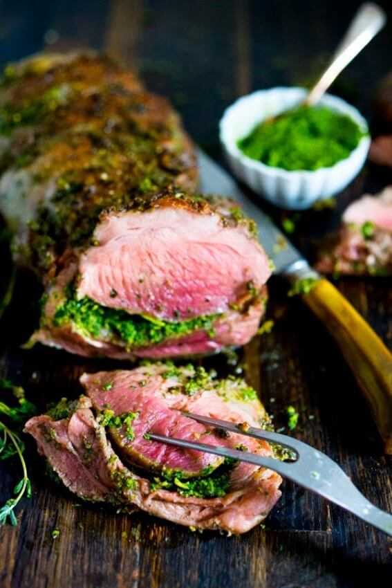 Herb Crusted Leg of Lamb sliced with green sauce