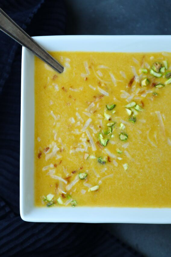 Top view of Keto Curried Squash Soup in square white bowl with pistachios and coconut
