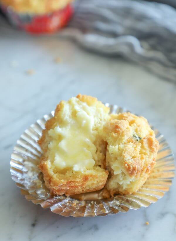 Keto Cheesy Herb Muffin cut in half and slathered in butter