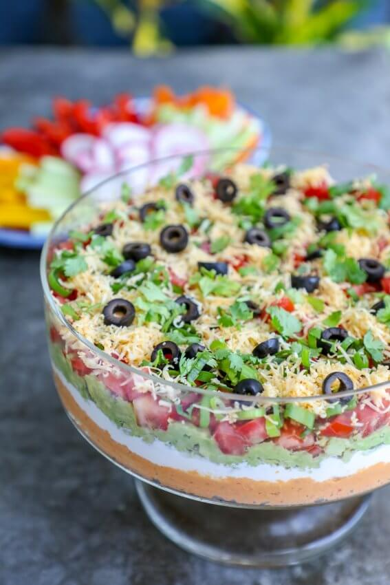 Keto 7 layer dip in a clear trifle bowl