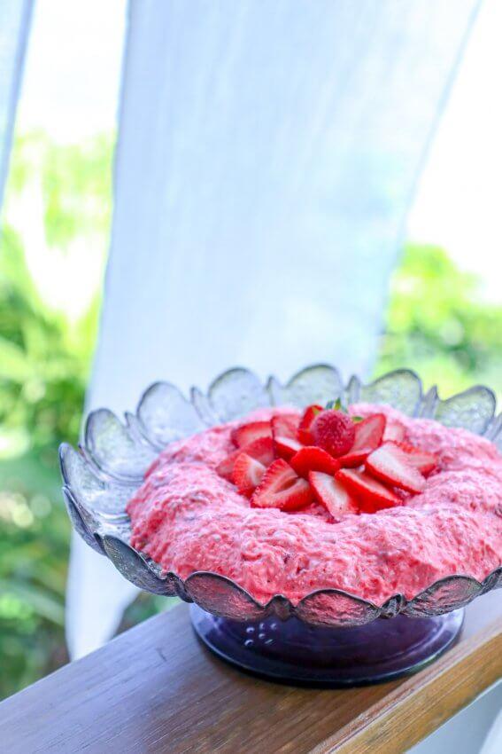 keto strawberry jello salad on railing with white curtain