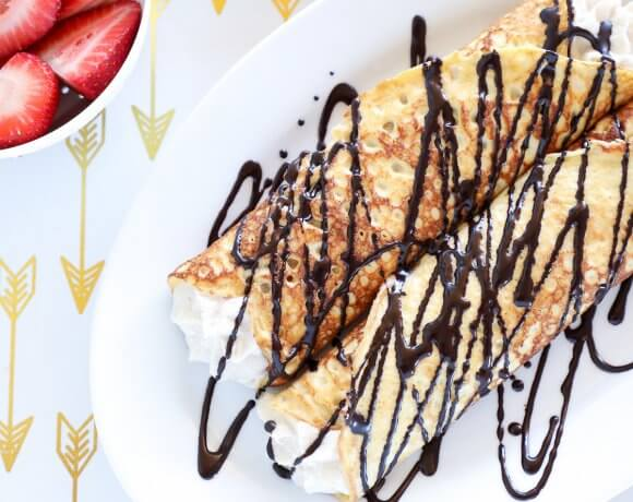 Keto Cannoli Stuffed Crepes on white tray with gold arrows