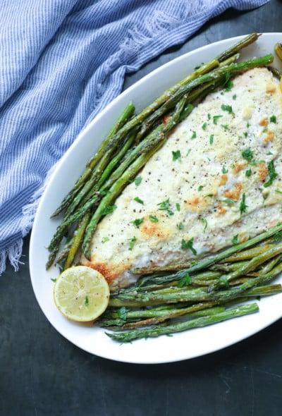 Keto Sheet Pan Salmon & Asparagus with lemon wedges on a white platter