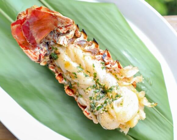 Keto Grilled Lobster Tails with Creole Butter on banana leaf