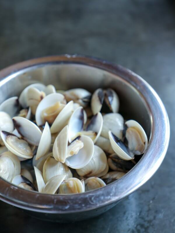Stainless bowl of baby clams in shells