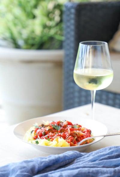 Keto Spaghetti Squash Puttanesca on a patio table with white wine