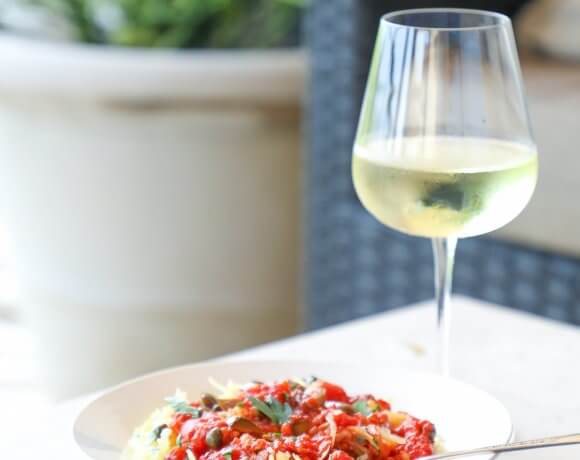 Keto Spaghetti Squash Puttanesca on a patio table with white wine