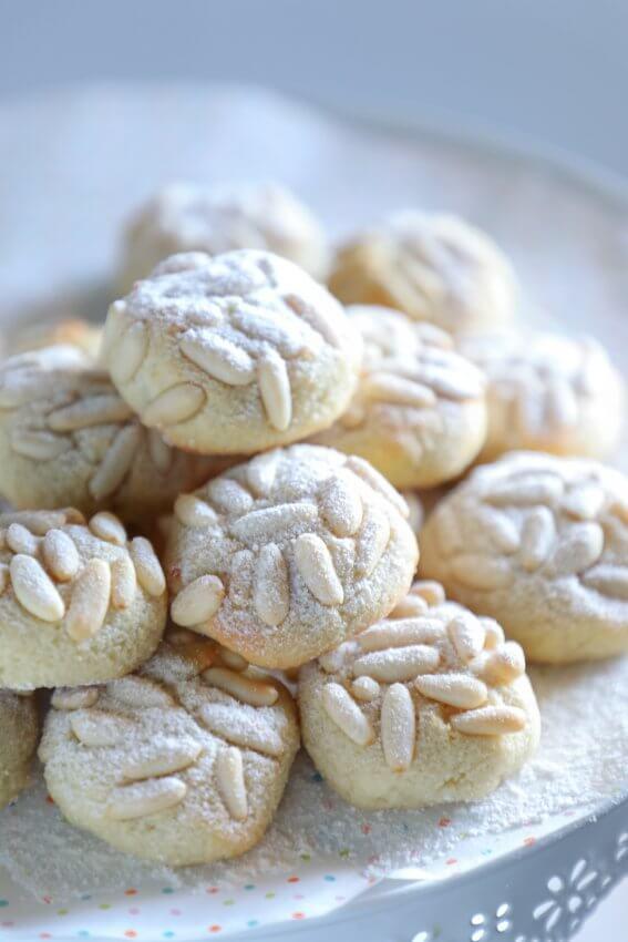 keto pignoli cookies on a white cake plate