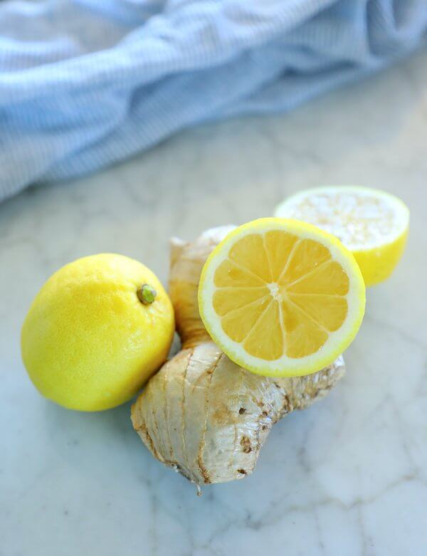 keto ginger lemon detox drink - lemons and ginger on a marble board