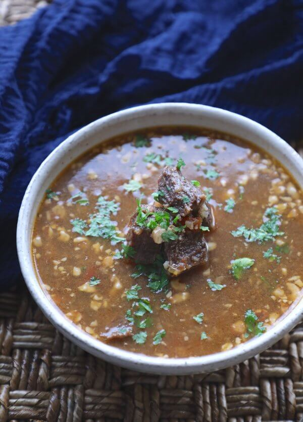 Instant Pot Keto Beef Barley Soup on a textured brown background