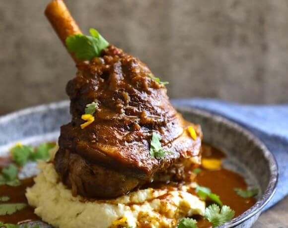 keto lamb shank shown with cauliflower puree on a blue granite enamelware plate
