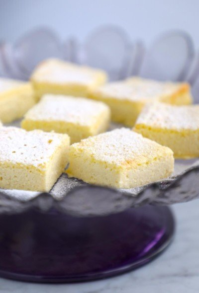 side view of Keto Lemon Magic Custard Cake on a purple cake stand