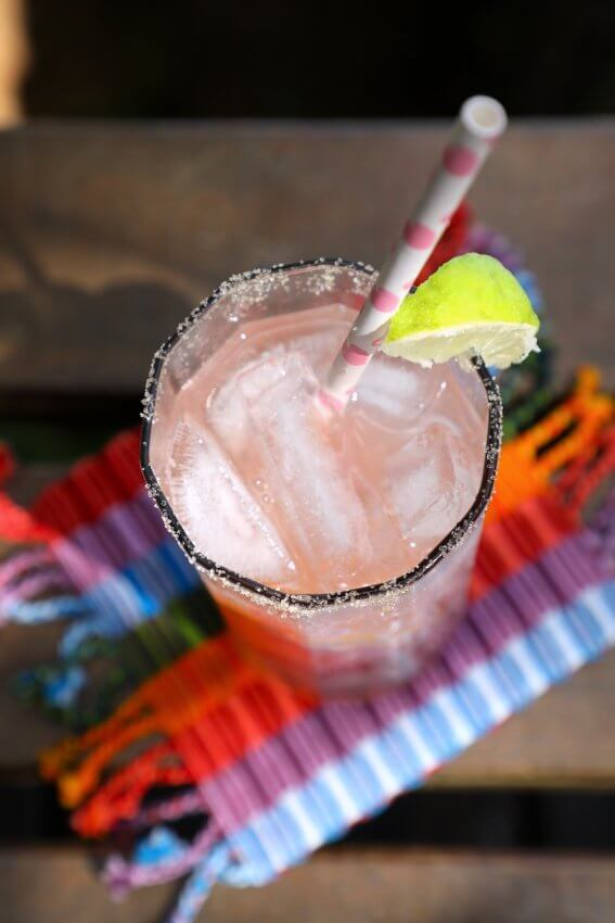 Top view of Keto Paloma Cocktail with pink and white paper straw and salted rim