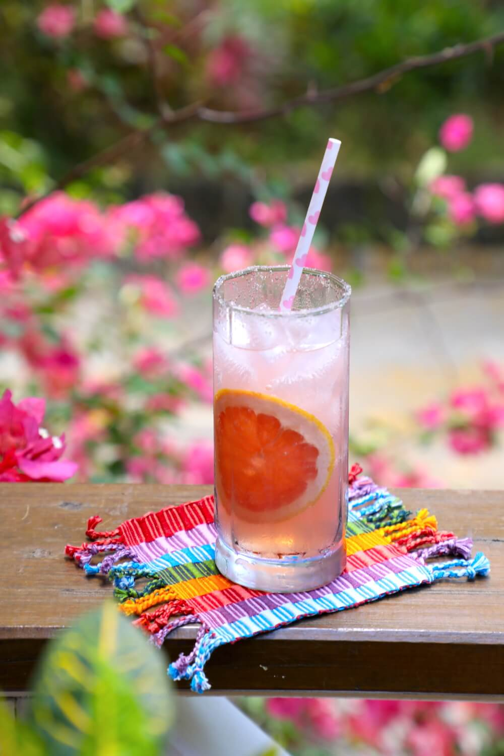 Keto Paloma Cocktail with pink flowers in the background