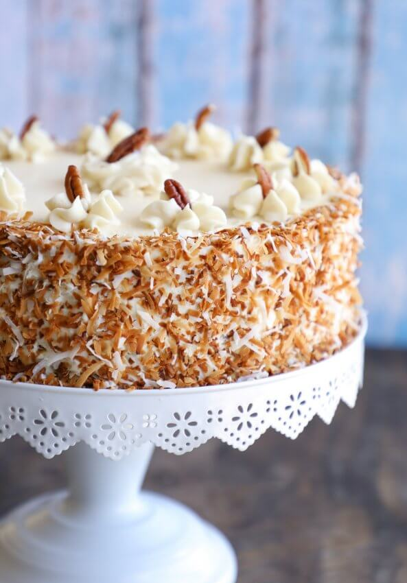 Keto Hummingbird Cake with toasted coconut garnish on a white cake pedestal