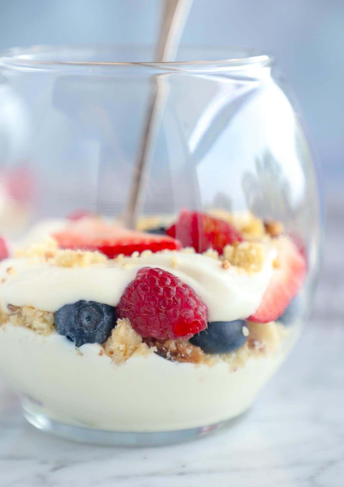 Side view of Keto No Bake Cheesecake Parfaits with fresh berries and cookie crumbs