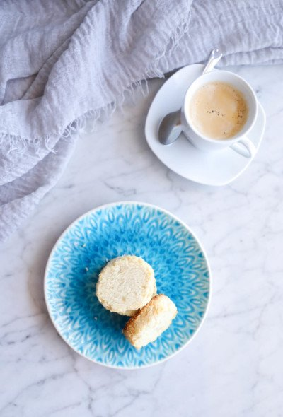 keto coconut shortbread cookies on a blue plate with a white espresso in the background