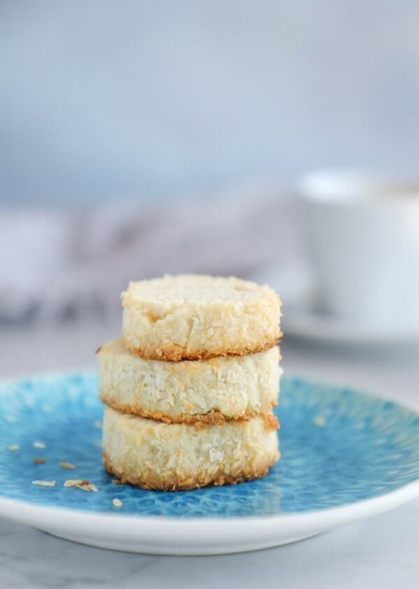 A stack of 3 keto coconut shortbread cookies on an aqua plate with a stamped design