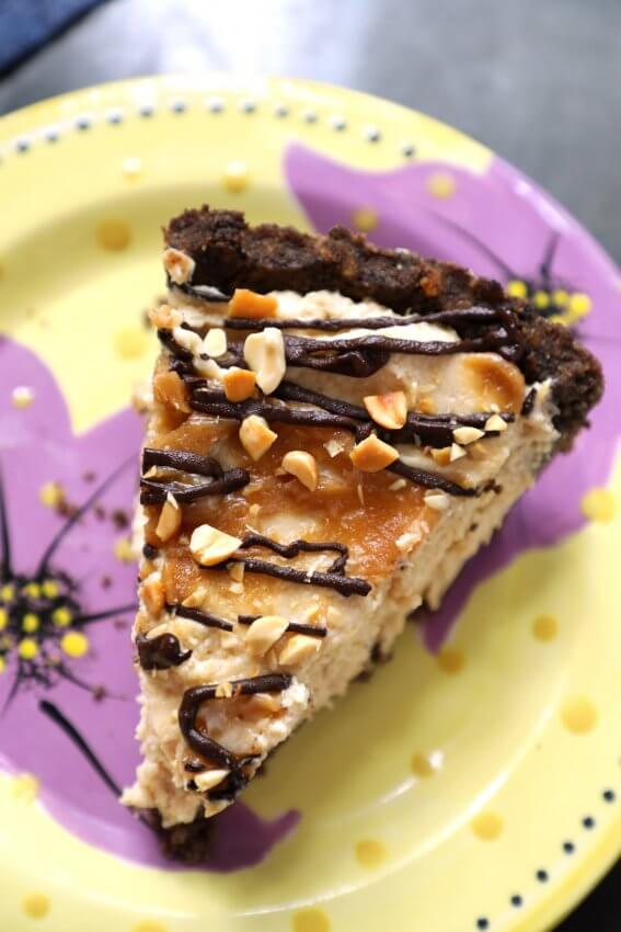 Top view of a slice of Keto Peanut Butter & Chocolate Pie on a yellow pottery plate with purple flowers on it.