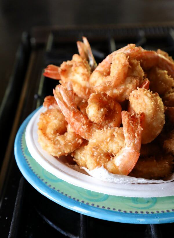 A big pile of Keto Coconut Shrimp fresh out of the fryer on a paper plate