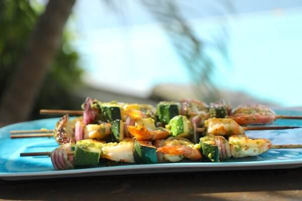 keto pesto shrimp skewers with palm trees in the background