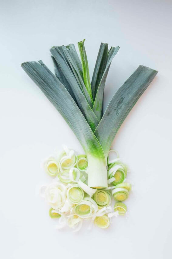 leeks partially sliced on a white background