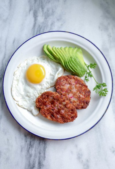 keto hash browns on a white plate with a fried egg and sliced avocado