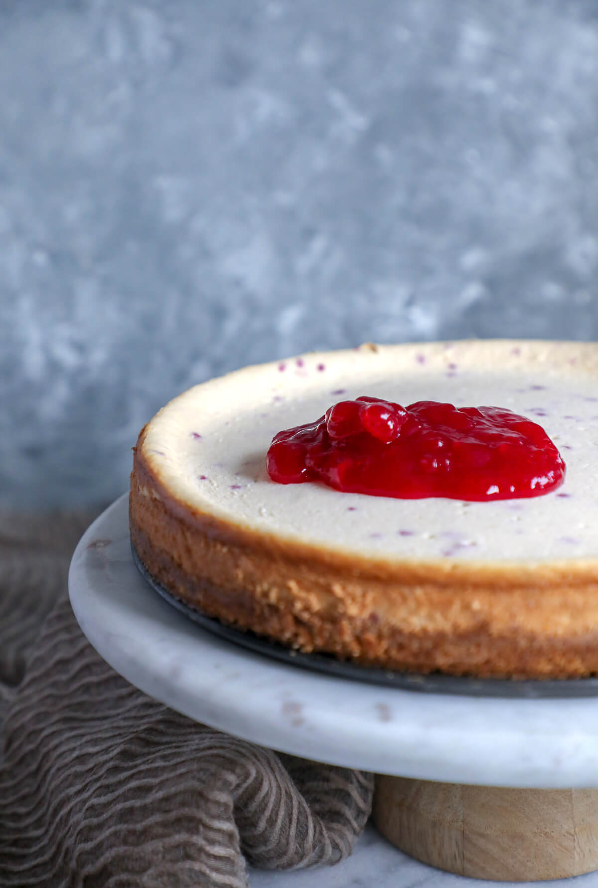 Process Shot of Keto cranberry orange cheesecake with the cranberry jelly spooned over the top