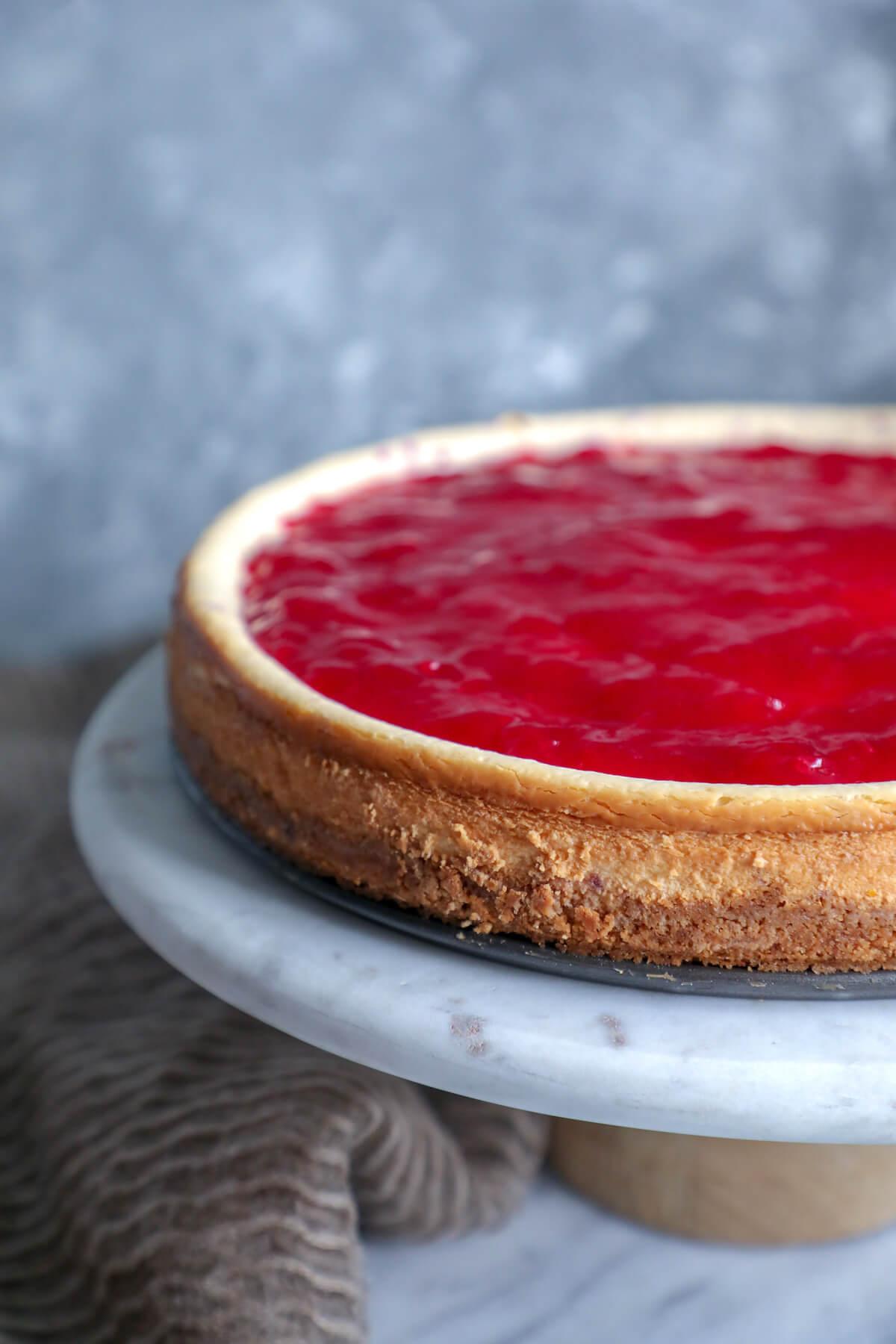 Keto cranberry orange cheesecake on a marble cake pedestal