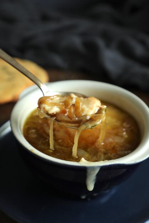 Spoonful of Keto French Onion Soup dripping with onions and cheese