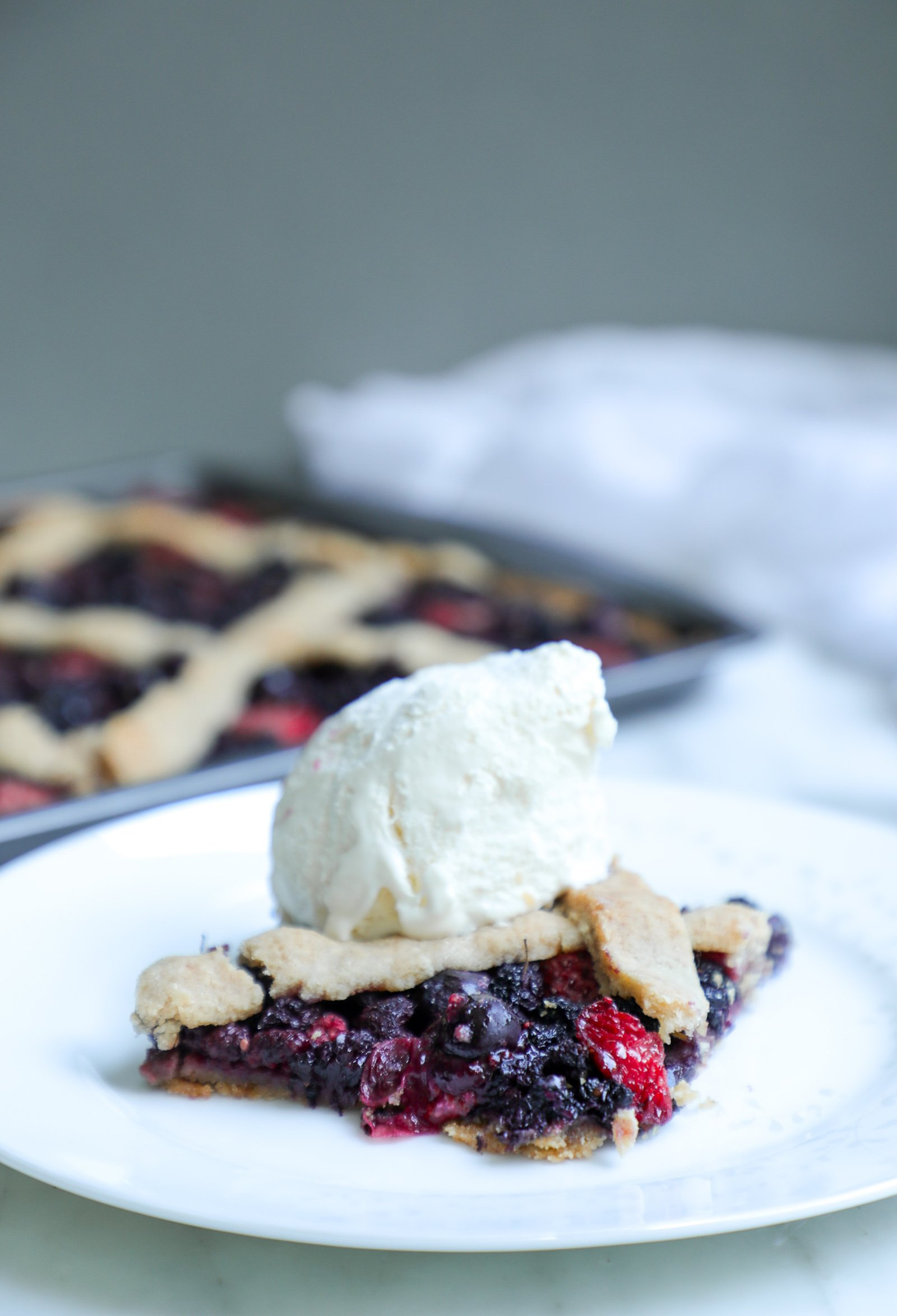 Keto Mixed Berry Slab Pie with low carb vanilla ice cream on top
