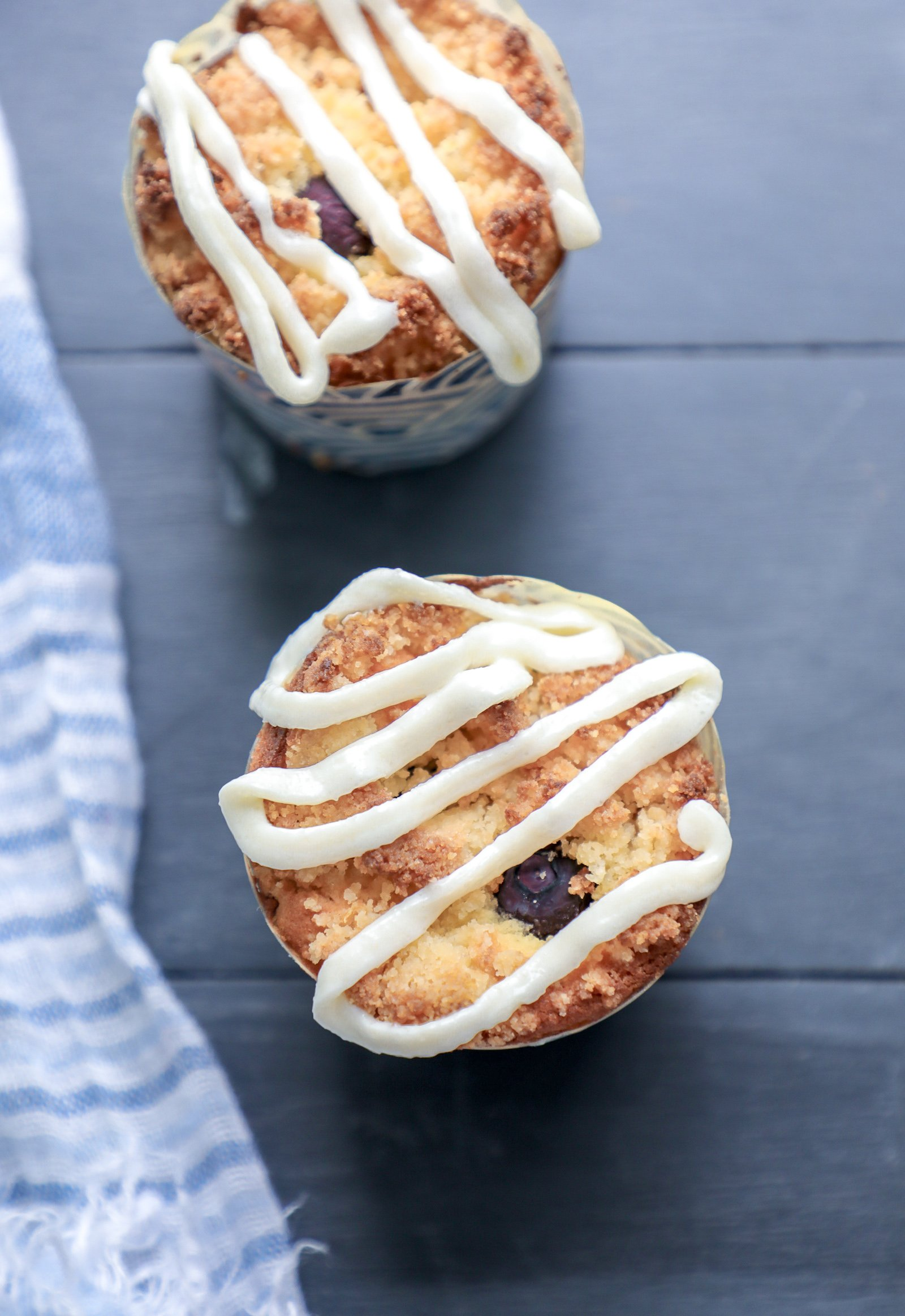 Top view of keto blueberry muffins with lemon icing